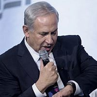Prime Minister Benjamin Netanyahu jokingly looks at his watch while speaking about peace in the Middle East at the National Building Museum November 9, 2015 in Washington, DC. (AFP/Brendan Smialowski)