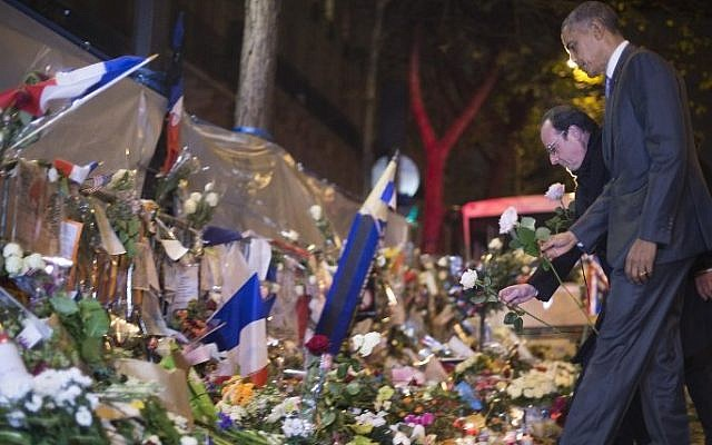 US President Barack Obama pays his respects with French President Francois Hollande and Paris Mayor Anne Hidalgo (not seen) at a memorial outside the Bataclan club in Paris , France, November 30, 2015. (AFP/ JIM WATSON)