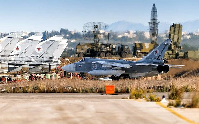 A Russian Su-24 fighter jet taxis at an air base near Latakia, Syria, with an alleged S-400 air defense battery in the background. (Russian Defense Ministry Facebook)