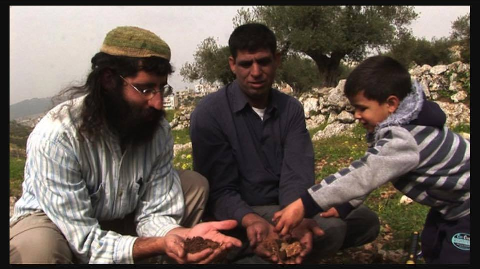 Muhammad Ziad Sabateen, right, as a young child plays with his father Ziad Sabateen, center, and Jewish peace activist Shaul Judelman from the 'Shorashim -- Judur -- Roots' organization. (Courtesy)