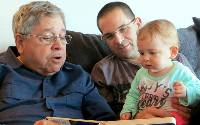 Richard Lakin (left) reads a book to his granddaughter, as his son Micah Avni looks on. January 2014. (Courtesy)