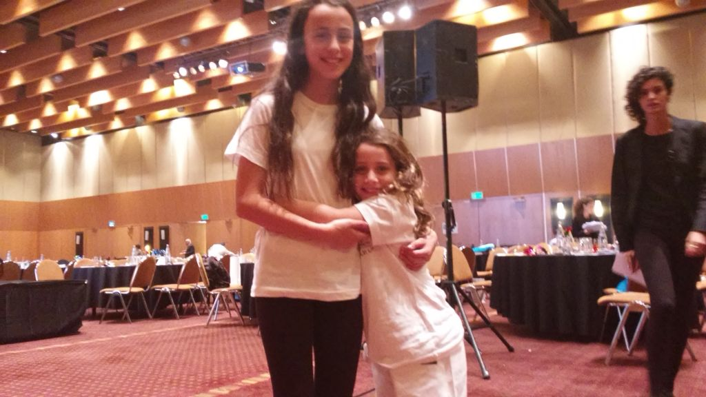 Kayla and Gefen Feiller performed on stage at the Tandem Capital Global Markets conference to raise awareness and money for Kids Kicking Cancer in Israel (Simona Weinglass/Times of Israel).