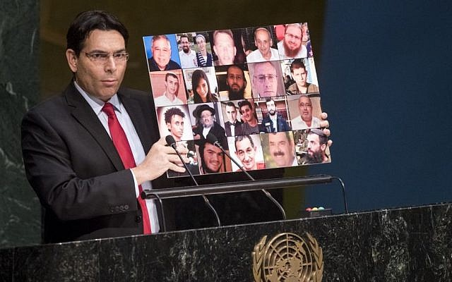 Israeli Ambassador to the UN, Danny Danon, holds up a collage of photos of Israeli terror victims killed in the ongoing surge of violence since mid-September, on November 23, 2015. (UN photo/ Cia Pak)