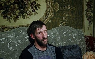 In this photo taken Thursday, Nov. 12, 2015, Abdulla Magomedov, brother of Rashid Magomedov who left to become an Islamic State fighter and was killed in Syria, sits at home in the village of Komsomolskoye, Dagestan, Russia. (Sergei Grits/AP)