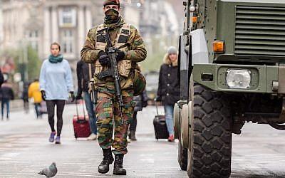 A Belgian Army soldier patrols on a main boulevard in Brussels, Sunday, Nov. 22, 2015. (AP Photo/Geert Vanden Wijngaert)