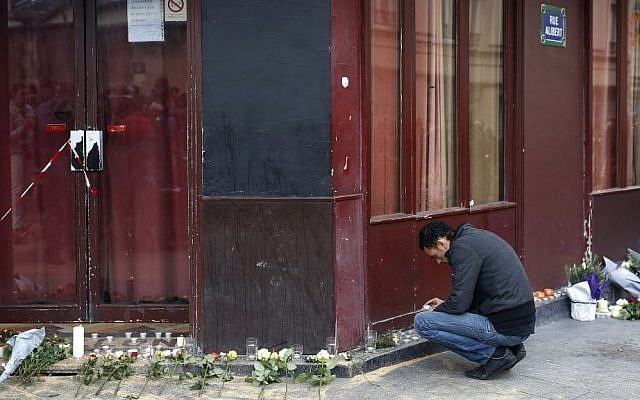 A man places a candle in front of the Carillon cafe in Paris Saturday Nov. 14, 2015, a day after over 120 people were killed in a series of shootings and explosions. (AP Photo/Jerome Delay)
