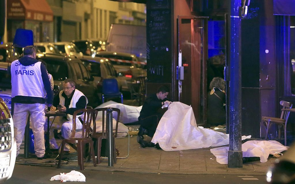 Victims lay on the pavement outside a Paris restaurant, Friday, Nov. 13, 2015. Police officials in France on Friday reported multiple terror incidents, leaving many dead. (AP Photo/Thibault Camus)
