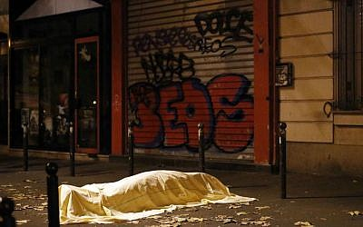 A victim under a blanket outside the Bataclan theater in Paris, Friday November 13, 2015. (AP Photo/Jerome Delay)