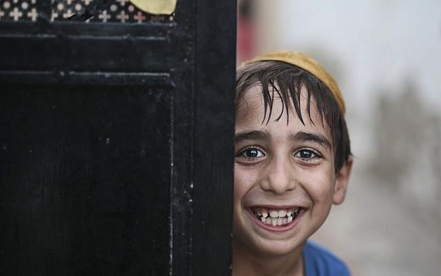 A student wearing a Kippah poses for the camera as he leaves the main Talmudic school at Hara Kbira, the main Jewish neighborhood on the Island of Djerba, southern Tunisia, October 29, 2015. (Photo by AP Photo/Mosa'ab Elshamy)