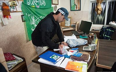 An Israeli police officer participates in a raid on offices of the Islamic Movement's northern branch overnight Monday, November 16, 2015 (Israel Police)