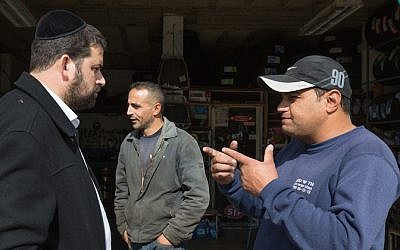 An ultra-Orthodox Jewish man from the Israeli settlement of Beitar Illit seen talking with Arabs as he gets his car washed at the Hussan Junction Palestinian-owned car wash in the West Bank, on November 11, 2015. (Nati Shohat/Flash90)