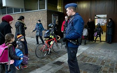 Children pass a police officer as they arrive for school in the center of Brussels on Wednesday, Nov. 25, 2015. (AP Photo/Virginia Mayo)