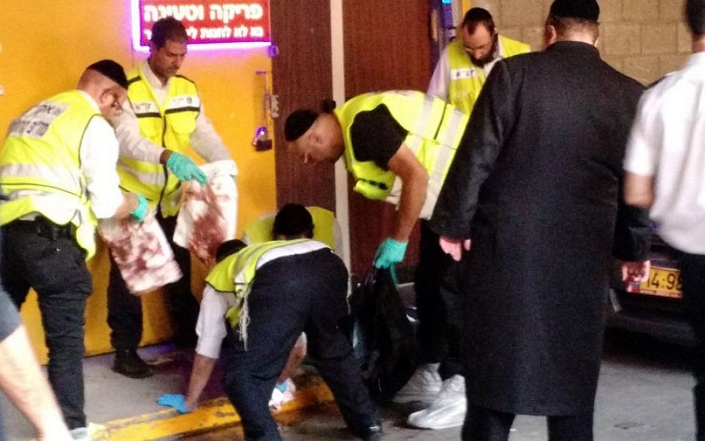 Members of the independent emergency service ZAKA cleaning blood at the scene of a stabbing attack in Tel Aviv on November 19, 2015. (Judah Ari Gross/ Times of Israel)