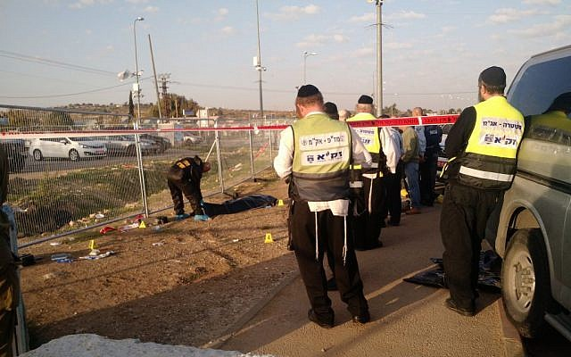 Members of the independent emergency service ZAKA wait for permission to begin cleaning blood and remains from the scene of a stabbing attack at the Gush Etzion Junction on November 22, 2015. (Judah Ari Gross/ Times of Israel)