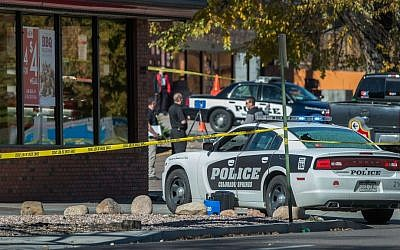 The rear window of a police car is shattered after a shooting Saturday, Oct. 31, 2015, in Colorado Springs, Colorado that left several people dead, including a suspected gunman. (Christian Murdock/The Gazette via AP)