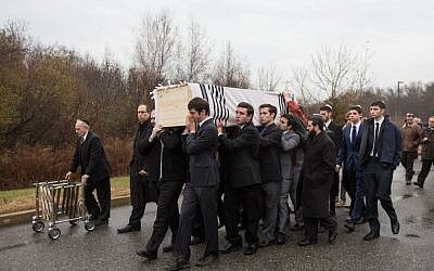 Following the funeral of Ezra Schwartz, 18, an American yeshiva student who was murdered in a Palestinian terror attack in Israel last week, friends carry the slain teen's casket outside Temple Sinai in Sharon, Massachusetts on November 22, 2015 (Elan Kawesch/The Times of Israel)