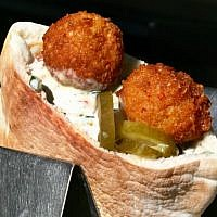A falafel sandwich ready to be eaten, part of the pantheon of Israeli food. (Orel Cohen/Flash90)