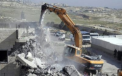 Illustrative: Bulldozers of the Jerusalem Municipality destroy a Palestinian house in the East Jerusalem neighborhood of A-Tur on March 26, 2014. (Sliman Khader/Flash90)
