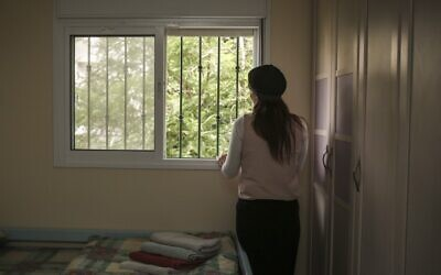 An Orthodox Jewish woman looks out the window of her room in an abused women's shelter in Beit Shemesh, July 15, 2014 (Hadas Parush/Flash90)