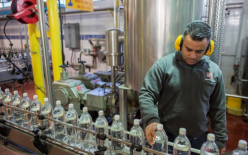 Palestinians work at a Superdrink factory on January 22, 2015 in Atarot industrial park, outside Jerusalem. (Yonatan Sindel/Flash90)