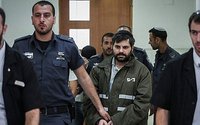 Police escort Yosef Ben David (in green), one of the Jewish suspects in the murder of Muhammed Abu Khdeir, in the Jerusalem District Court on June 8, 2015. (Hadas Parush/Flash90)