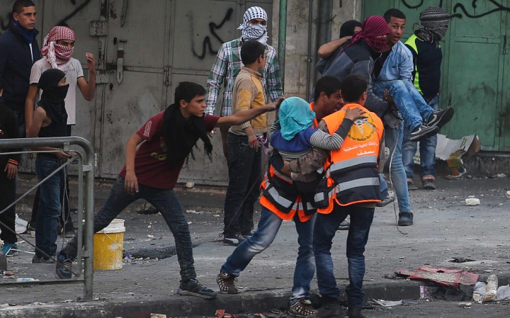 Palestinians carry a man wounded in clashes with Israeli soldiers in the West Bank city of Hebron, October 31, 2015. (Flash90)