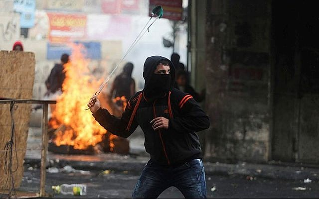 Palestinian protesters use slingshots to hurl stones towards Israeli troops during clashes in the West Bank city of Hebron, November 5, 2015. (by Flash90)