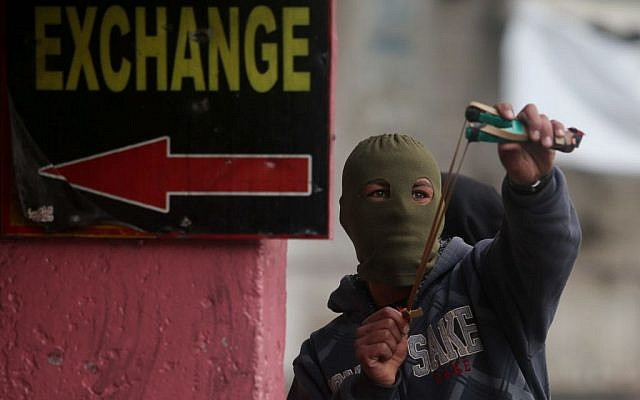 A Palestinian use a slingshot to hurl stones towards Israeli troops during clashes in the West Bank city of Hebron, November 5, 2015. (Flash90)
