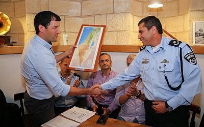 West Bank settlement council CEO Sheila Adler, left, shakes hands with Deputy Commissioner Shlomi Michael, right, police commander of the Judea and Samaria District during a meeting security situation, in the West Bank, November 9, 2015. (Gershon Elinson/Flash90