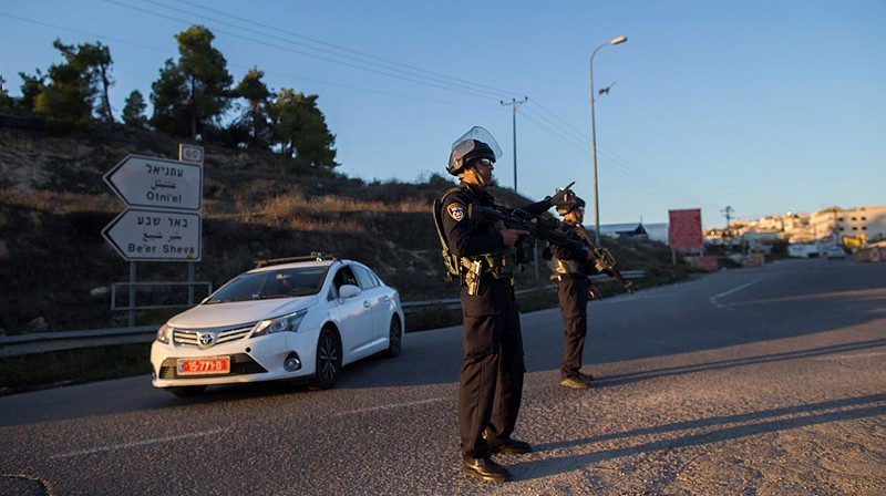 Israeli security police stand near the Otniel Junction in the southern West Bank where an Israeli man and his 18-year old son were killed and five others wounded when a Palestinian terrorist fired on their vehicle south of the West Bank city of Hebron, on November 13, 2015. (Yonatan SIndel/Flash90)