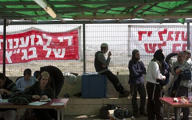 """Right wing activists seen at the Ayelet Hashahar synagogue in the West Bank settlement of Givat Ze'ev, sit in front of signs reading """"Stop the discrimination of the High Court,"""" on November 16, 2015. (Lior Mizrahi/Flash90)"""