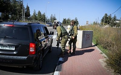 IDF soldiers inspect a Palestinian vehicle at a temporary checkpoint set up near the Jewish settlement of Alon Shvut, in the Etzion Bloc of the West Bank on November 22, 2015. (Gershon Elinson/FLASH90)