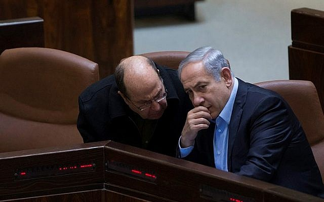 Prime Minister Benjamin Netanyahu speaks with Defense Minister Moshe Ya'alon (L) in the assembly hall of the Knesset on November 24, 2015. (Yonatan Sindel/Flash90)