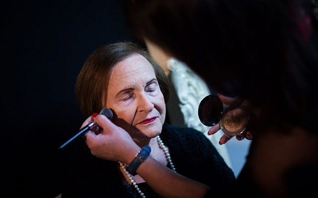 Naomi Licthoiz getting her makeup done ahead of a a Holocaust survivors beauty pageant in Haifa on November 24, 2015. (Yonatan Sindel/Flash90)