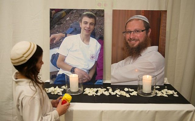 A child looks at the photos of terror victims Rabbi Ya'akov Litman, 40, and his son Netanel, 18 who were killed on November 13, 2015 in a terror attack, at the wedding of Sarah Litman and Ariel Biegel. (Hadas Parush)