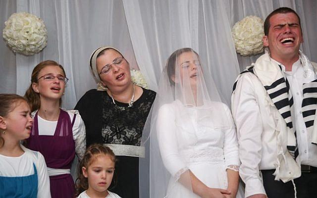 Bride Sarah Litman and groom Ariel Beigel sing during the wedding ceremony at the Jerusalem International Convention Center on November 26, 2015. (Hadas Parush/Flash90)