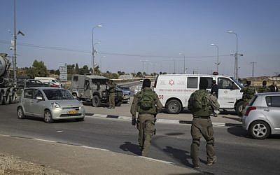 Israeli security forces at the scene where a Palestinian driver rammed his car into Israeli soldiers near Beit Ummar in the West Bank, on November 27, 2015. (Photo by Gershon Elinson/Flash90)