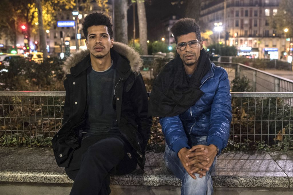 In this photo taken on Sunday, Nov. 15, 2015, Khaled Saadi, 27, left and Abdullah Saadi, 38, listen during an interview with the Associated Press. Khaled Saadi was working in La Belle Equipe restaurant, where his sister was celebrating her birthday, when the attackers assualted the cafe. 35-year-old Halima died on the spot. 36-year-old Hodda was severly wounded and barely breathing, and Saadi did everything he could to try to save her. In vain. (AP Photo/Kamil Zihnioglu)