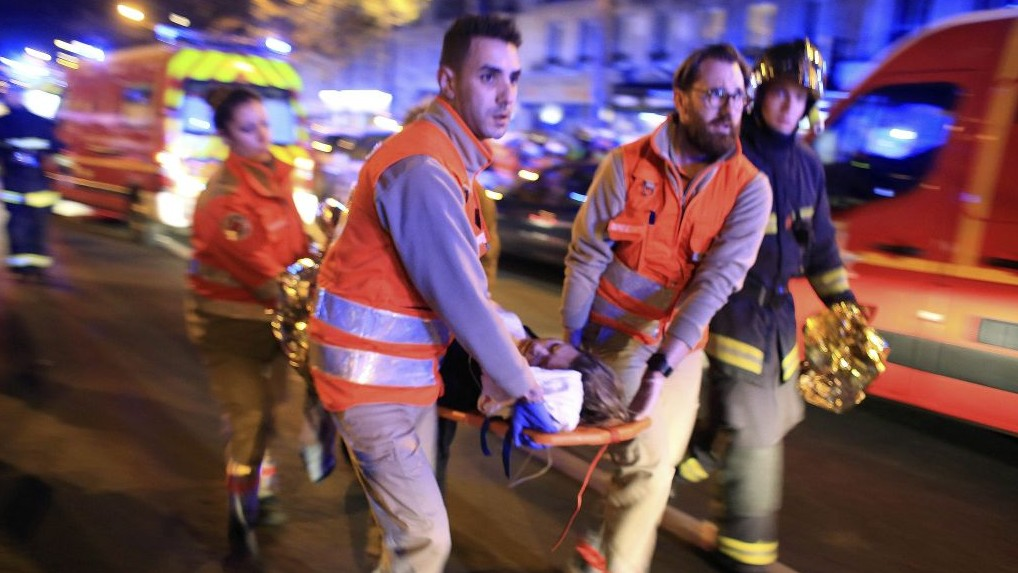 A woman is evacuated from the Bataclan concert hall after a terrorist shooting attack in Paris, November 13, 2015. (AP Photo/Thibault Camus, File)
