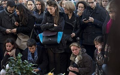 People pay their respect to the victims at the site of the attacks on restaurant Le Petit Cambodge (Little Cambodia) and the Carillon Hotel on the first of three days of national mourning in Paris, Sunday, Nov. 15, 2015. (AP Photo/Peter Dejong)