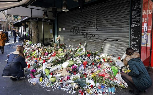 Flowers and candles in memory the victims of terror attacks two days earlier are placed in front of the restaurant on Rue de Charonne, Paris, Sunday, November 15, 2015 (AP/Frank Augstein)