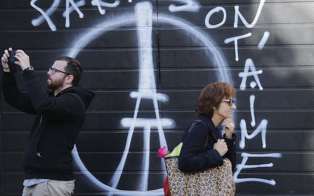 People pass a painting on a garage door opposite the restaurant on Rue de Charonne, Paris, Sunday, Nov. 15, 2015, where attacks took place on Friday. (AP/Frank Augstein)