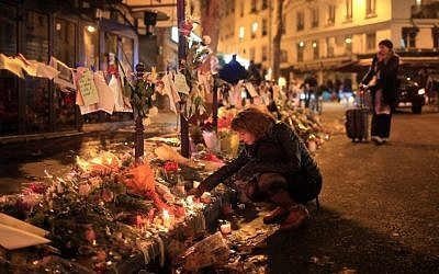 A woman lights a candle near the Cosa Nostra restaurant in Paris, France, on November 20, 2015. (AP/Thibault Camus)