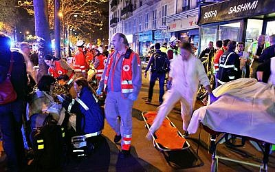 People rest on a bench after being evacuated from the Bataclan theater after a shooting in Paris, Saturday, Nov. 14, 2015.  (AP Photo/Thibault Camus)