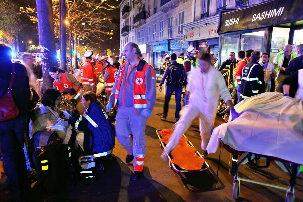 People rest on a bench after being evacuated from the Bataclan theater after a shooting in Paris, November 14, 2015. (AP Photo/Thibault Camus)