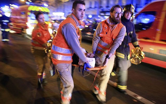 A woman is being evacuated from the Bataclan theater after a shooting in Paris, Friday November 13, 2015. (AP Photo/Thibault Camus)