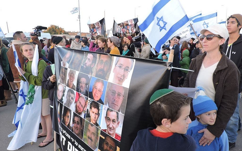 Protesters in Gush Etzion holding a poster of Israelis killed in terrorist attacks, Nov. 23, 2015. (Ben Sales)