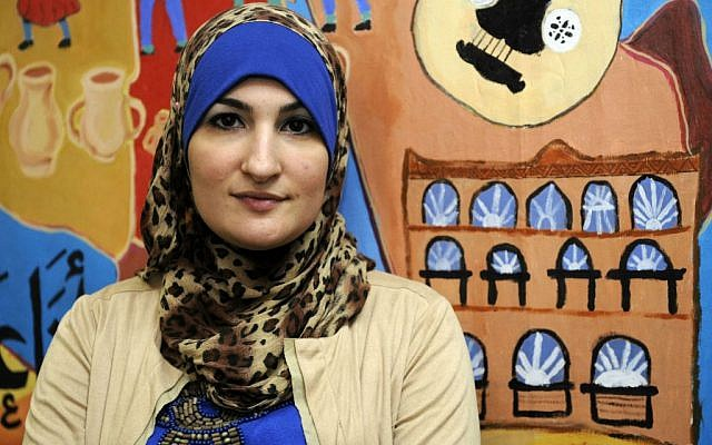 In this Dec. 29, 2011 file photo, Linda Sarsour, director of the Arab American Association of New York, poses for photos in front of a canvas painted by the association's youth group at its headquarters in the Brooklyn borough of New York. (AP Photo/Henny Ray Abrams, File)