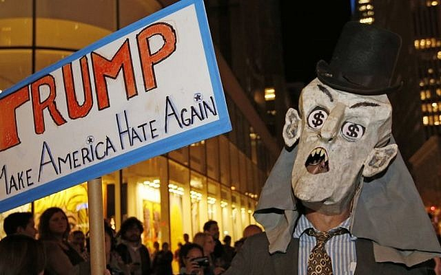 "A protester wearing a puppet head with dollar signs in his eyes demonstrates across the street from NBC Studios where ""Saturday Night Live,"" is taped and broadcast, Wednesday, Nov. 4, 2015, in New York. (AP/Kathy Willens)"
