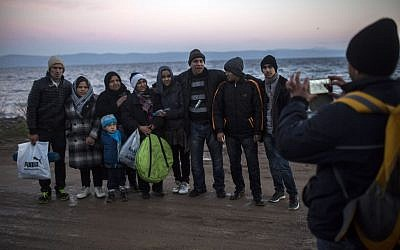 Afghan refugees take a group picture after their arrival on a dinghy, with other refugees and migrants, from the Turkish coast to the northeastern Greek island of Lesbos, November 30, 2015. (AP/Santi Palacios)